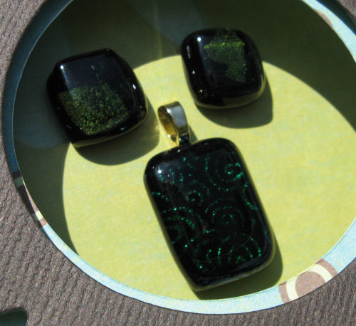 For the earrings I used black glass for the bottom later, then a bit of silver leafing, then transparent green on top. For the pendant I used black glass with a foil pattern and clear on top. The foil did no damage to my microwave in the kiln!