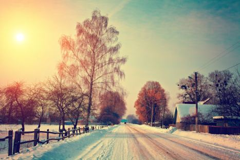 Snowy rural landscape with road at sunset